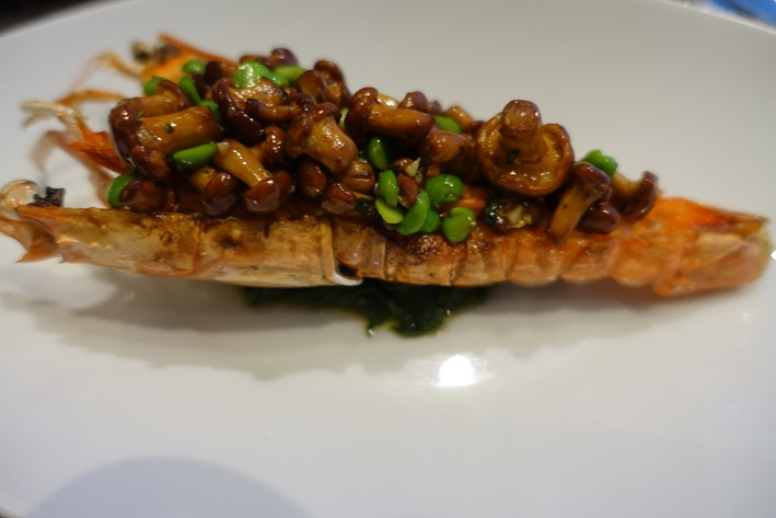 closeup of langoustine with girolles and peas