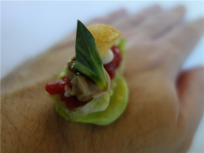 beef tartare served on diner's hand